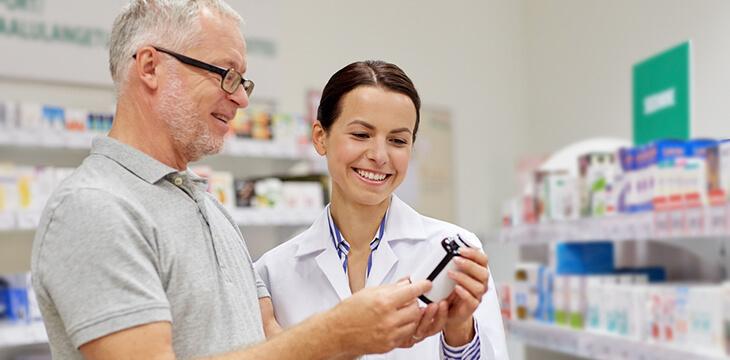 Женщина фармацевт помогает покупателю